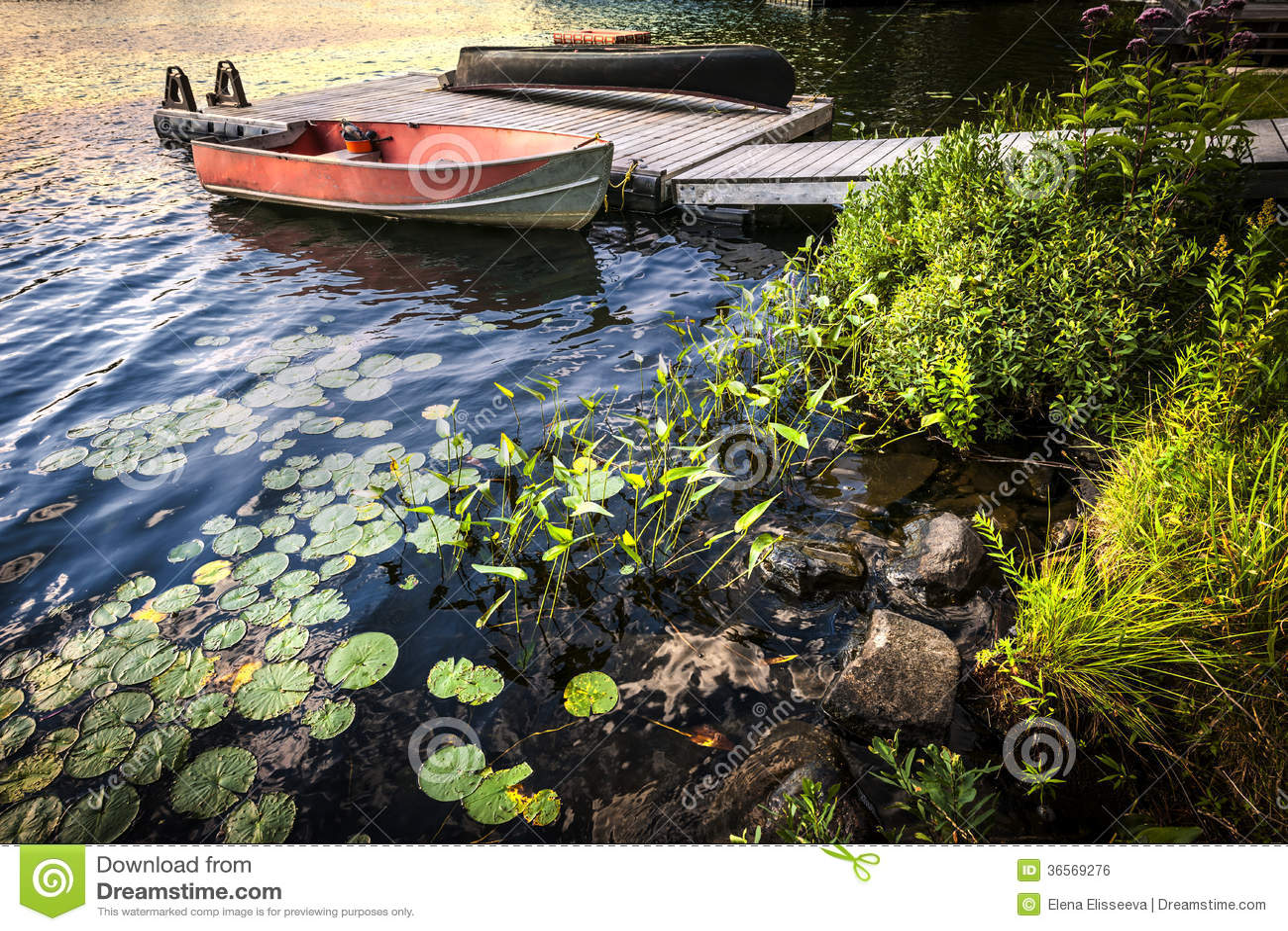 Bateau à rames au rivage de lac au crépuscule