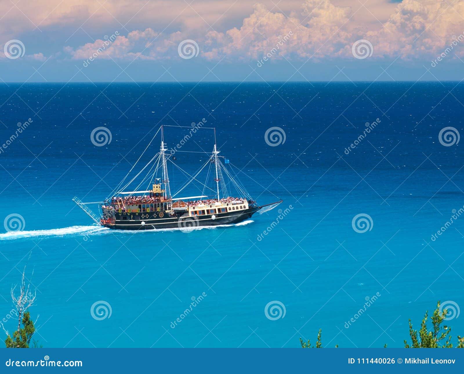 Bateau courant de bateau de style de corsaire de pirate en stupéfiant la baie d île de la Grèce avec les personnes de natation, p