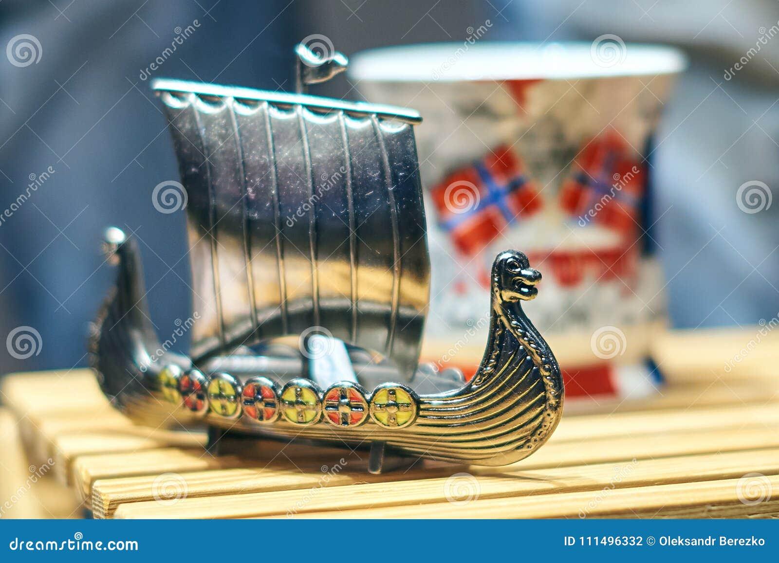 Bateau de jouet de Viking en métal également connu sous le nom de karve ou knarr et tasse norvégienne traditionnelle avec le drap