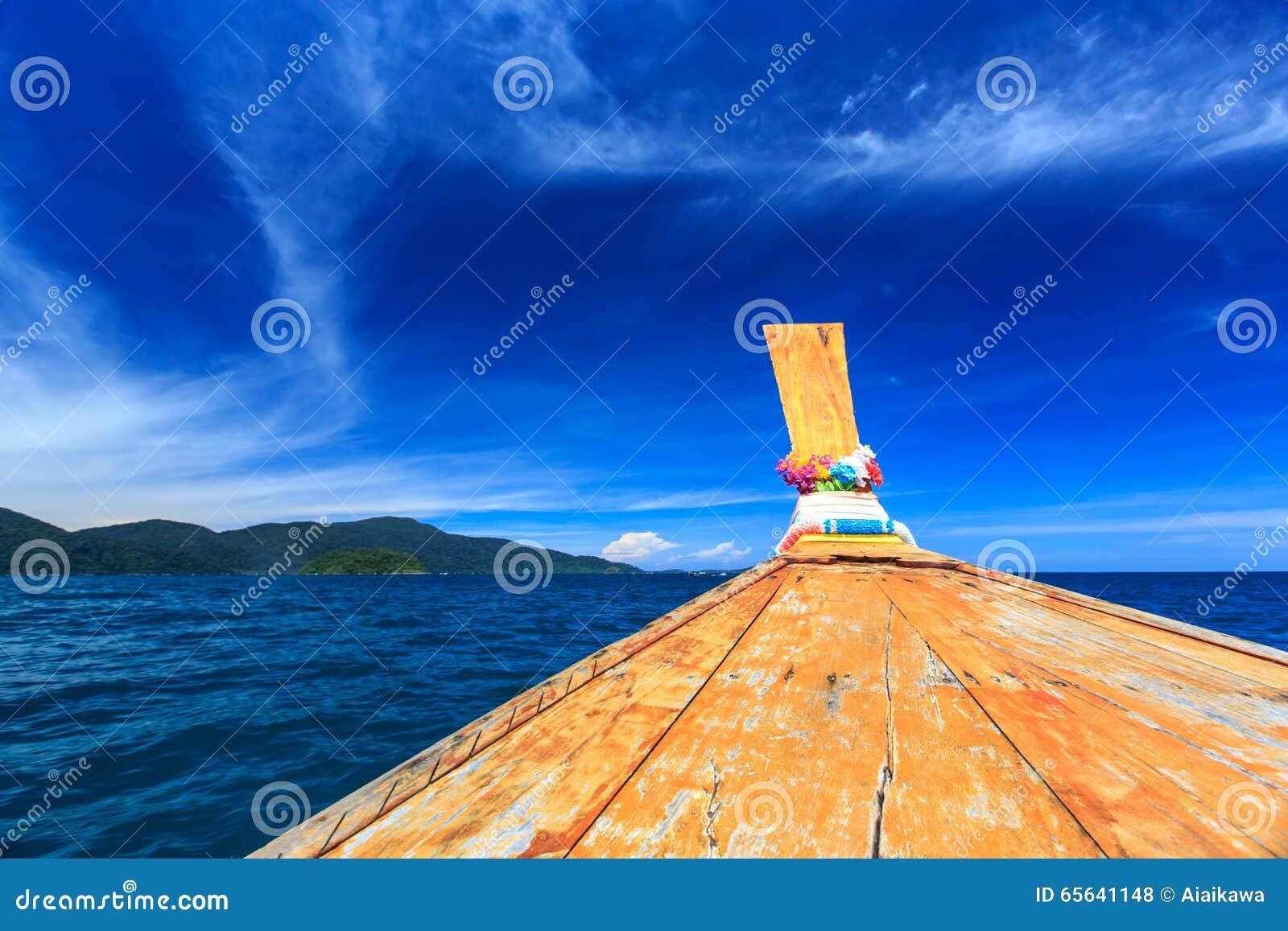 Bateau de Longtail sur la mer clair comme de l eau de roche à la plage tropicale