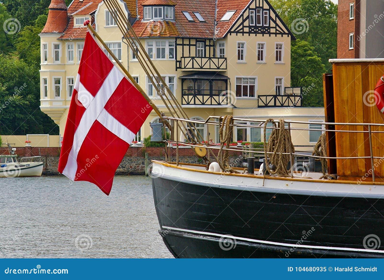 Bateau de navigation traditionnel avec le grand drapeau national danois pendant de la poupe dans le port de Sonderborg, Danemark