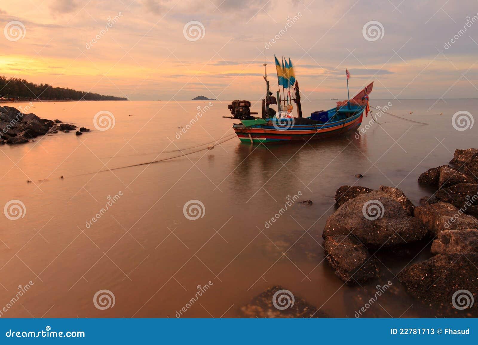 Bateau de pêcheur avec le coucher du soleil