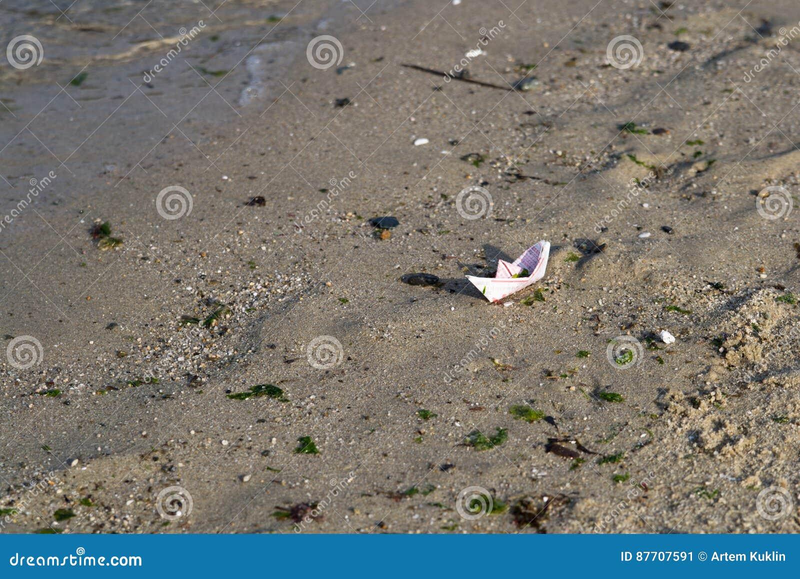 Bateau de papier sur une plage de sable