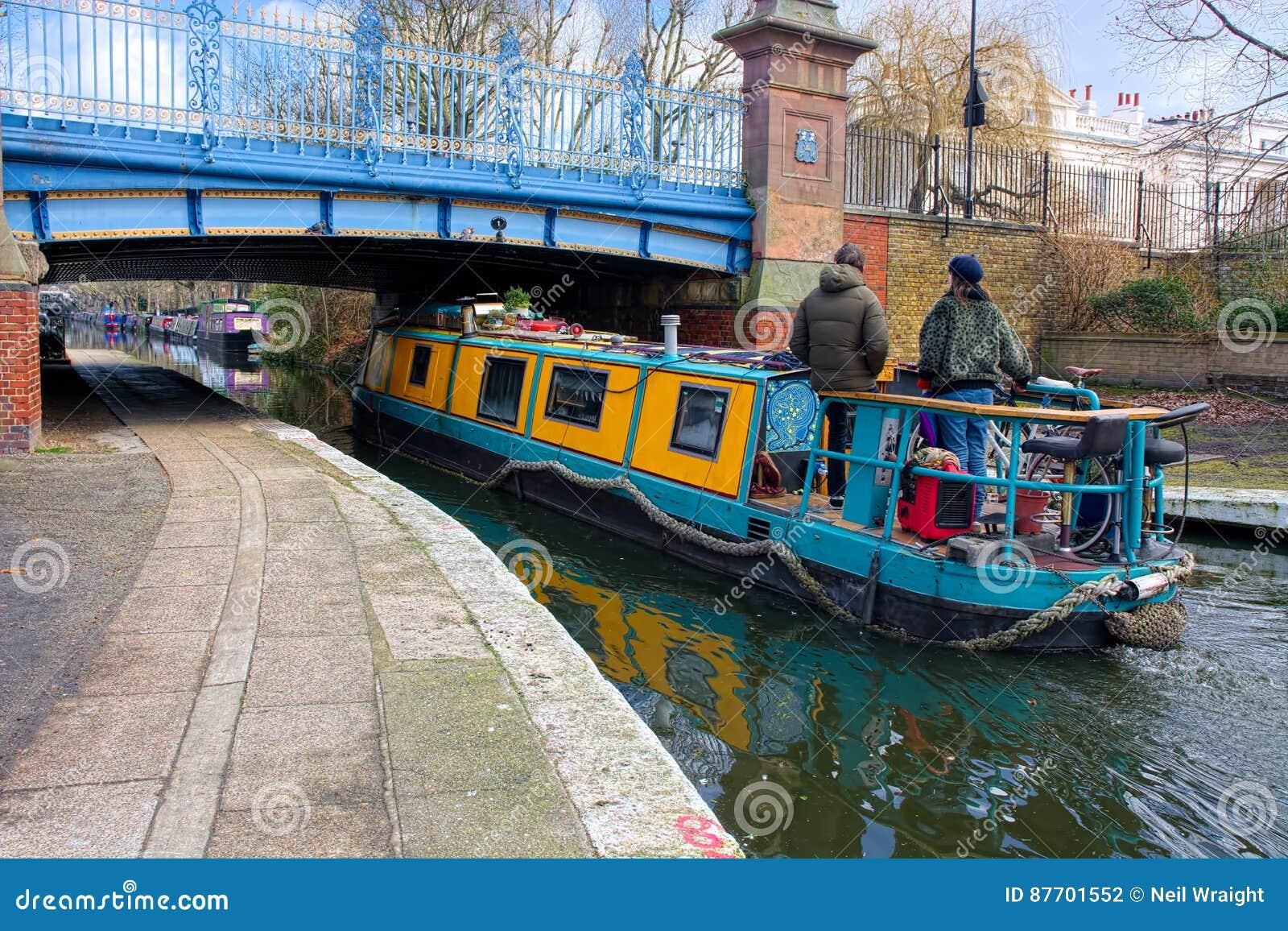 Bateau/péniche étroits de canal allant sous un pont