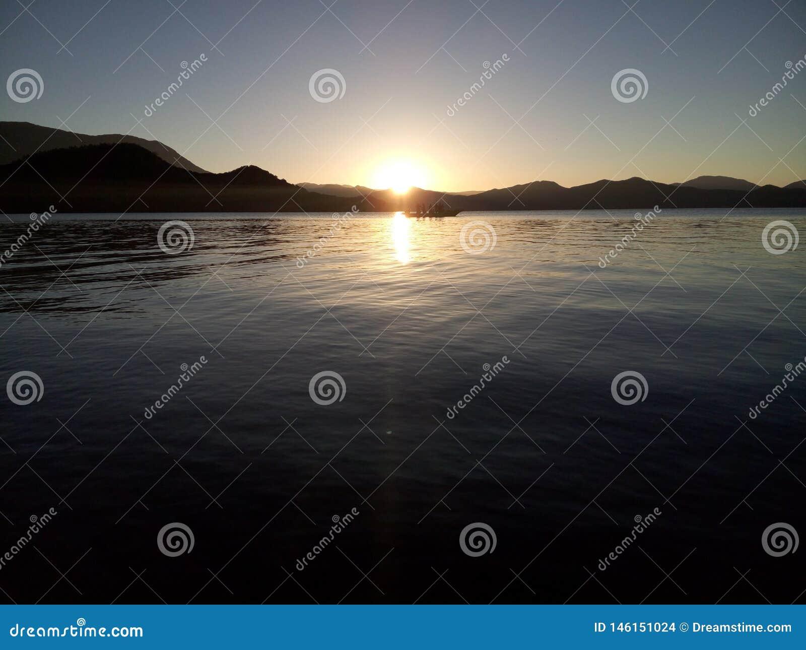 Bateaux de p?che retournant dans le coucher du soleil