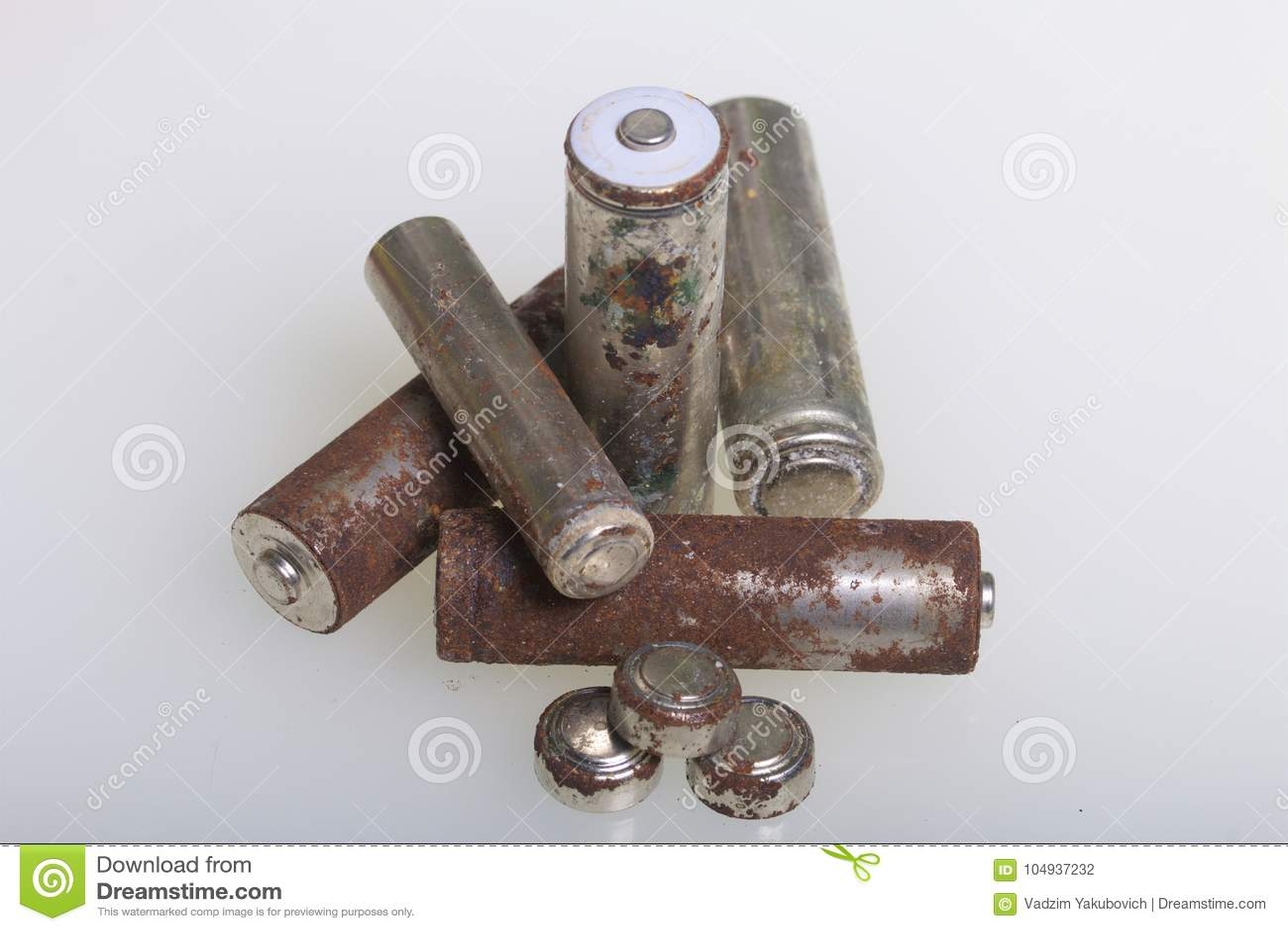 Baterias de corrosão de vários formas e tamanhos As mentiras afrouxam em um fundo branco Proteção ambiental, reciclagem do usado