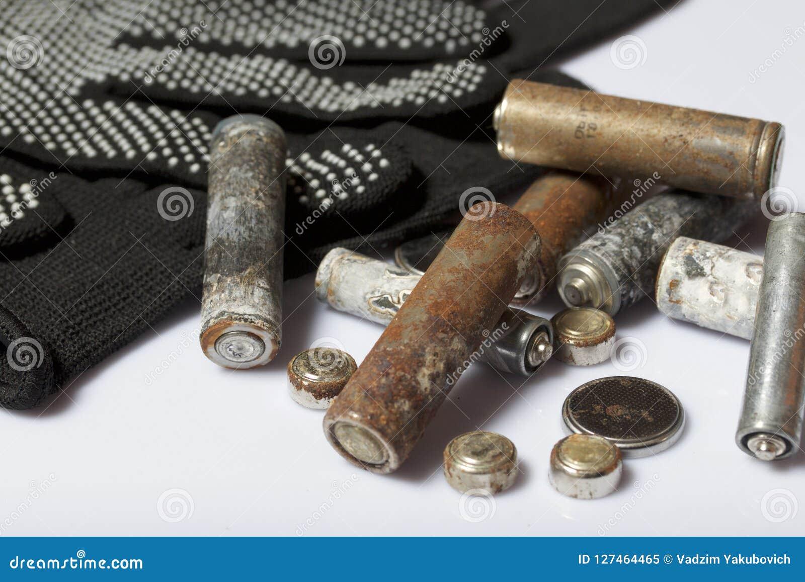 Baterias usadas da dedo-ferida cobertas com a corrosão Encontram-se em uma caixa de madeira Luvas de trabalho seguintes recycling
