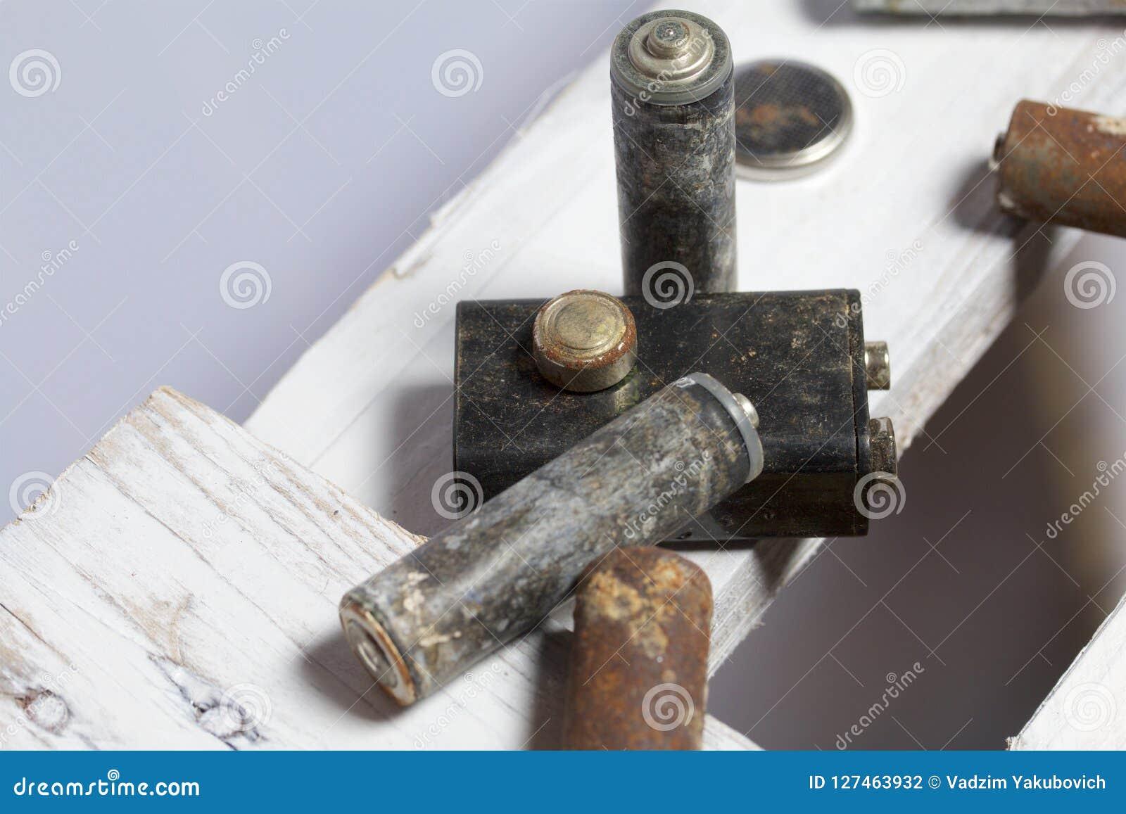 Baterias usadas da dedo-ferida cobertas com a corrosão Encontram-se em uma caixa de madeira recycling