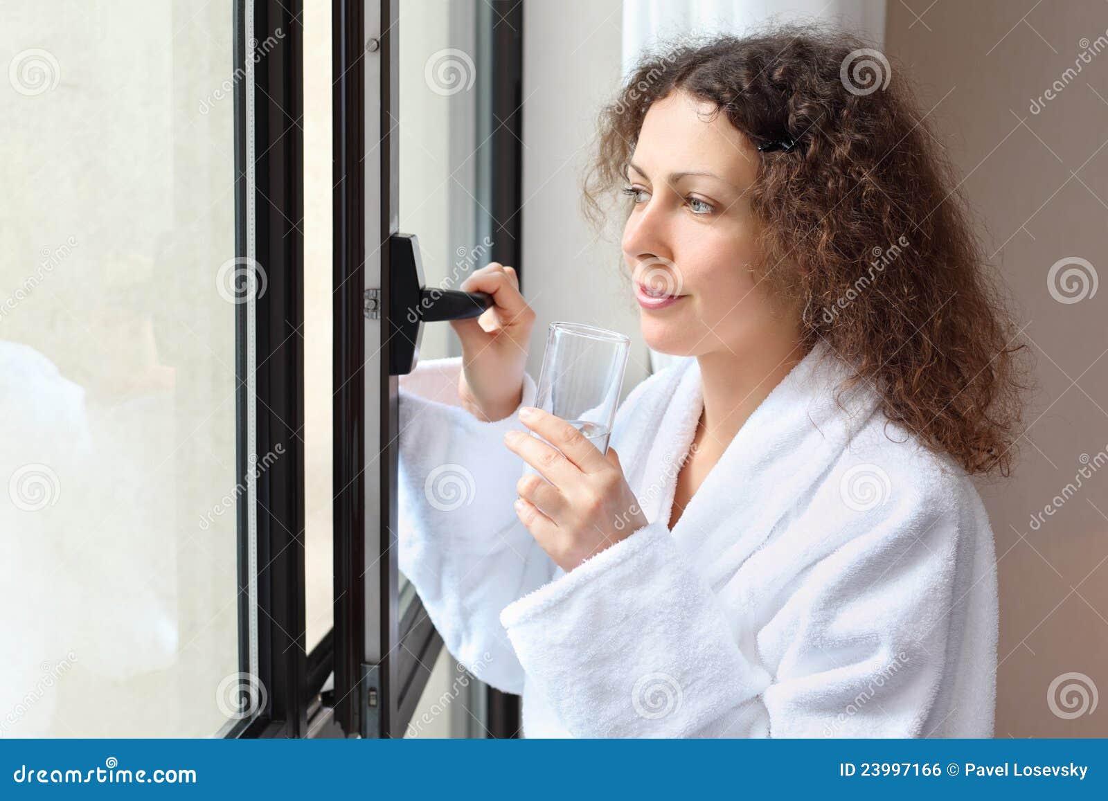 Bathrobe ubierający szkło trzyma białej kobiety