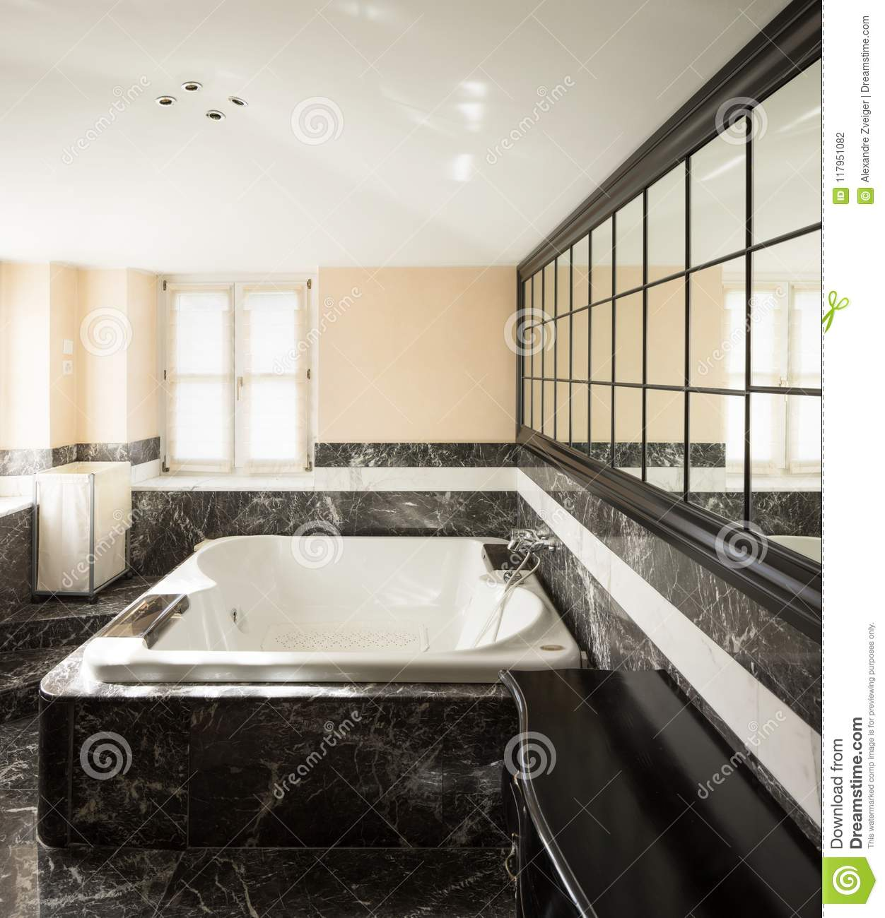 Bathroom With Black Marble Tiles And Empty Big Bathtub Stock Photo