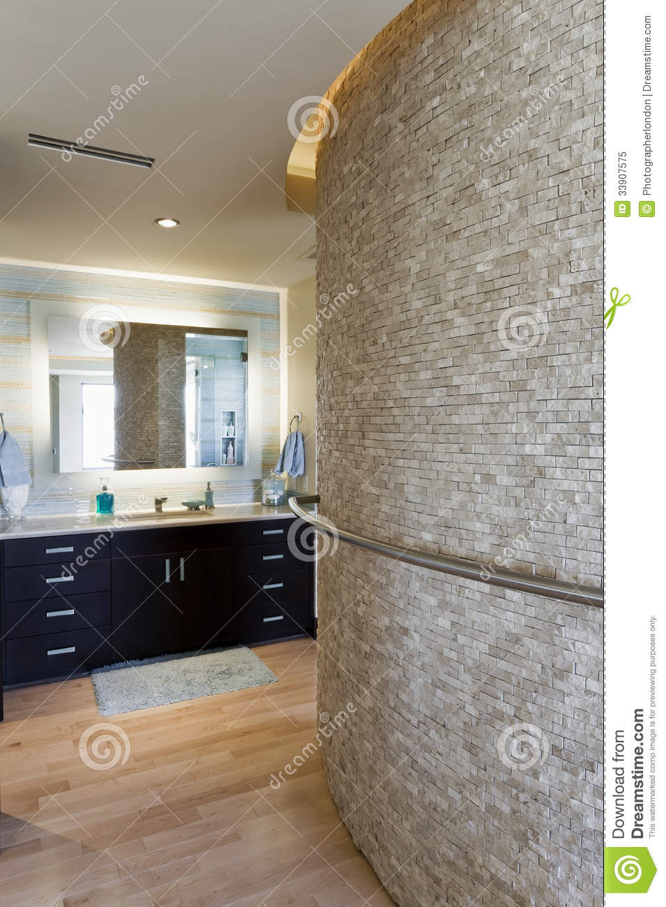 bathroom with curved stone wall and cabinets royalty free