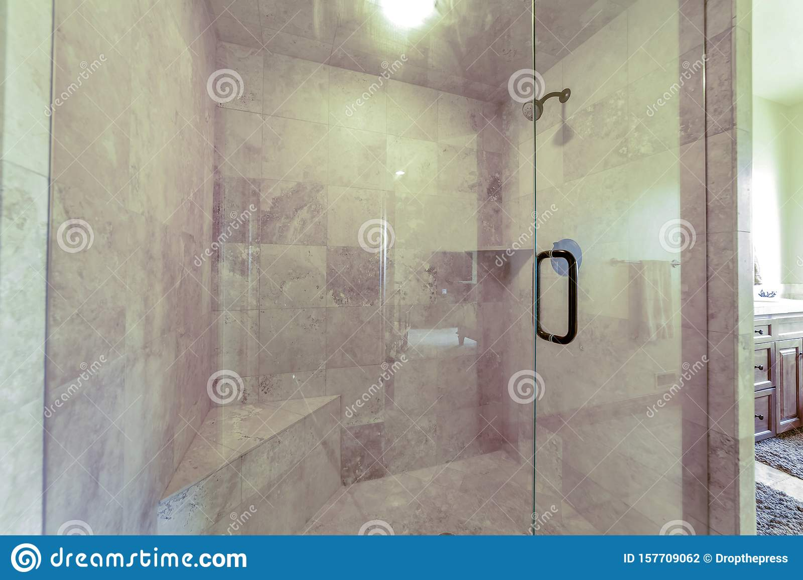 Bathroom Shower Stall With Glass Door And Gray And White Tiles On