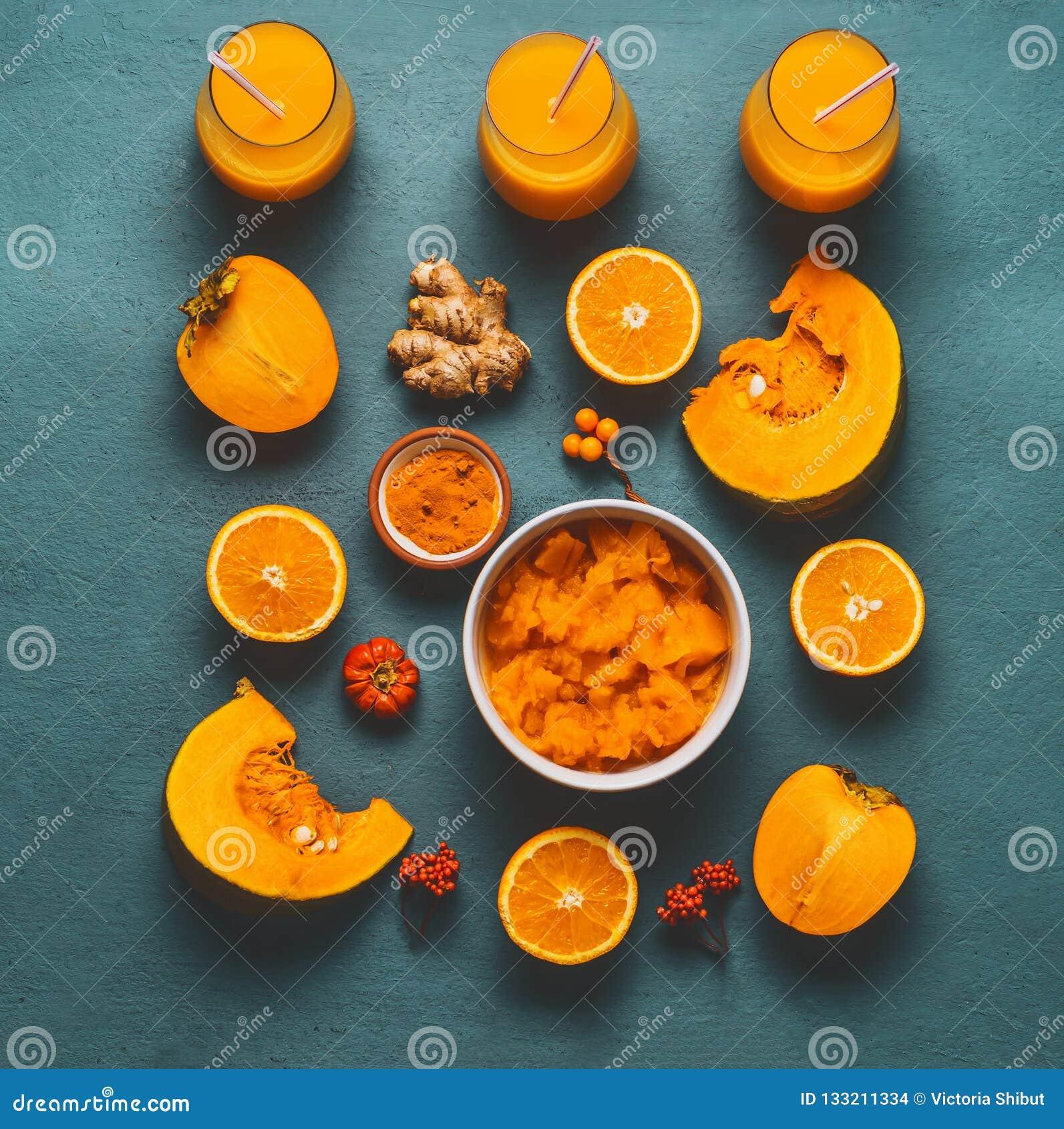 Batido saudável da abóbora com os ingredientes alaranjados da cor: caqui, pó alaranjado dos frutos, do gengibre e da cúrcuma