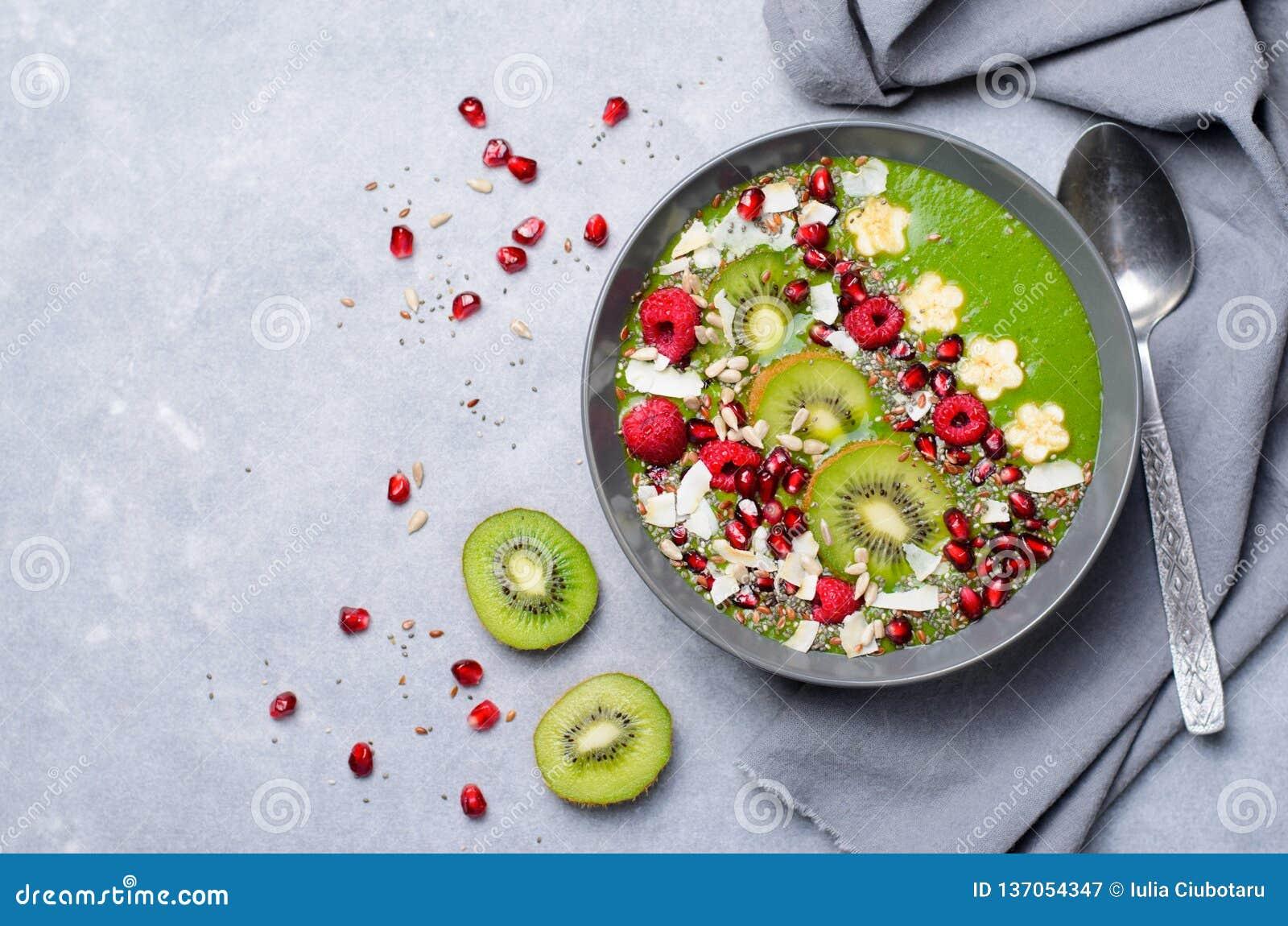 Batido saudável do verde da desintoxicação do café da manhã com banana e espinafres em uma bacia, vista superior