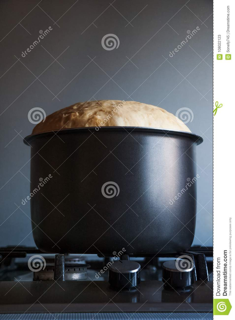 The batter dough in a black saucepan rises by leaps and bounds.
