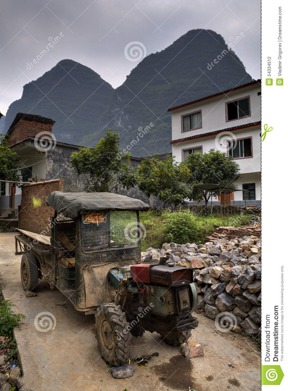 Chinese Antique Tractors : Battered ancient farmer tractor stands in peasant village