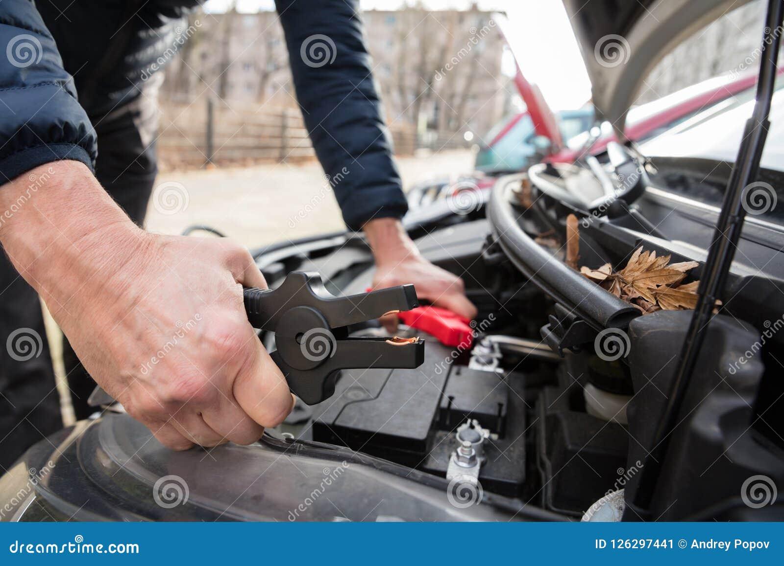 Batteri för ` s för Person Using Jumper Cables To laddningsbil dött
