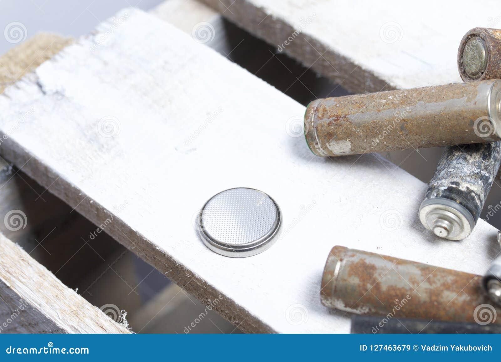 Batteries utilisées de doigt-blessure couvertes de corrosion Ils se trouvent sur une boîte en bois réutilisation