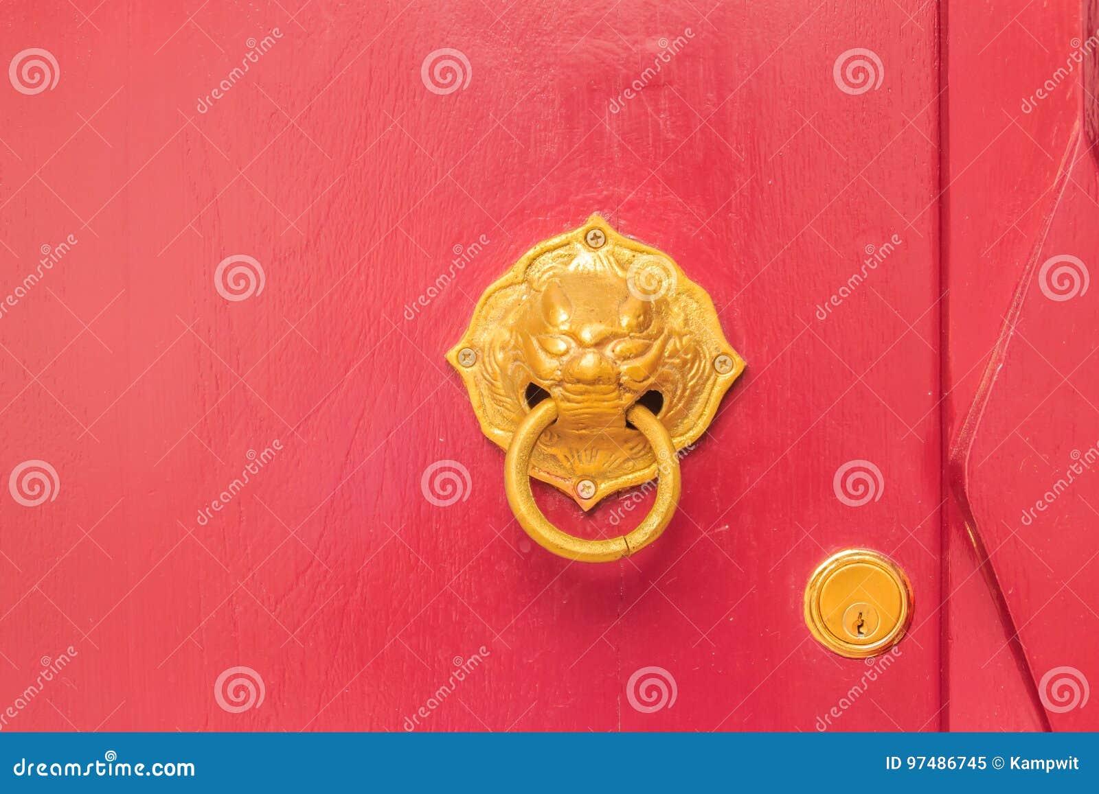 Battitore di porta dorato sotto forma del leone con l anello su un legno rosso