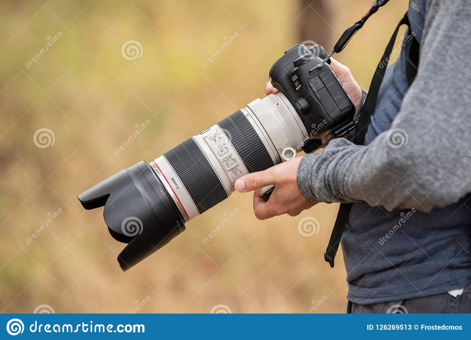 Person Holding Canon Camera With Telephoto Lens Editorial