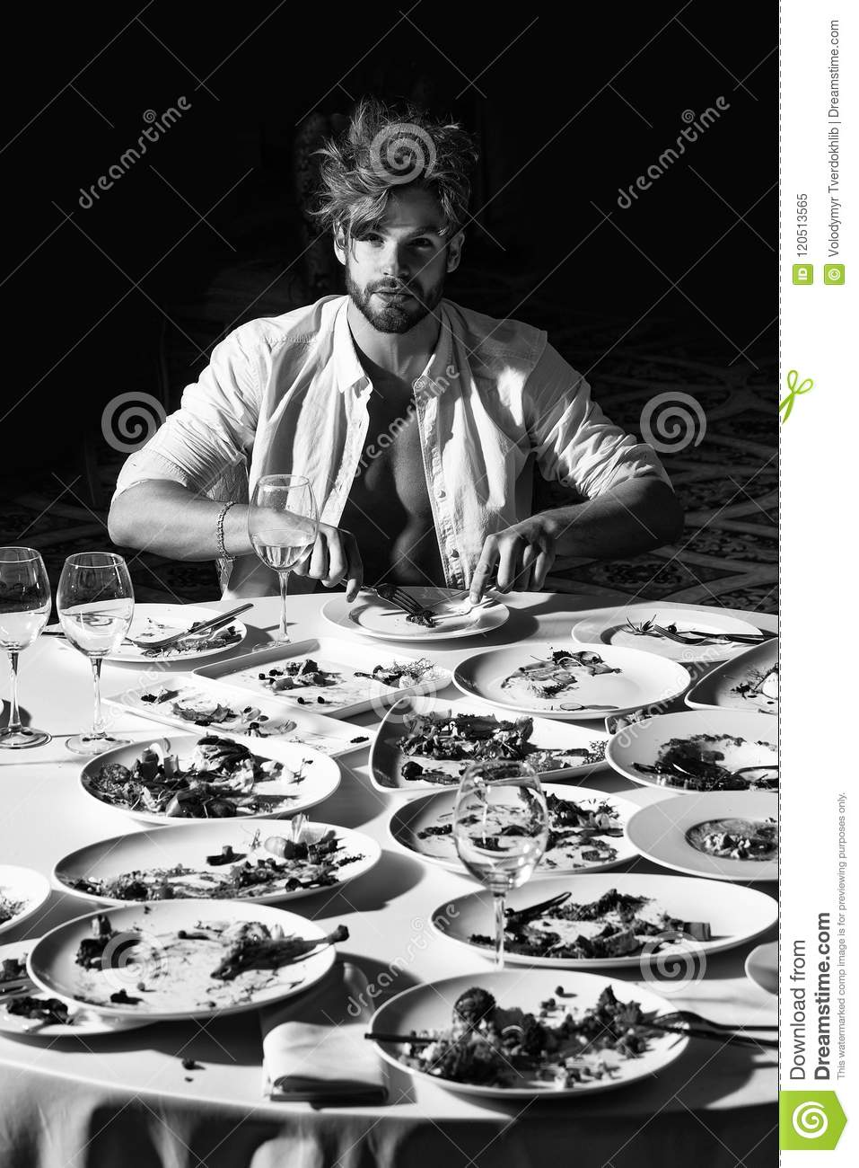 Battles of restaurateurs. Handsome man eats at table