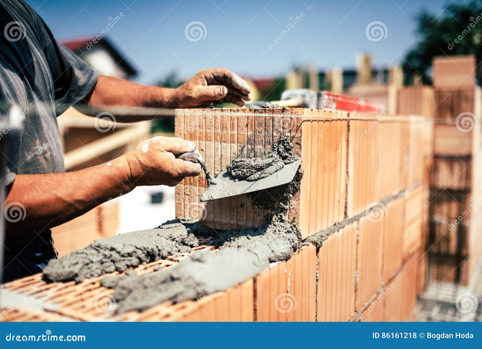 bauarbeiter, der spachtel und kelle für errichtende wände mit