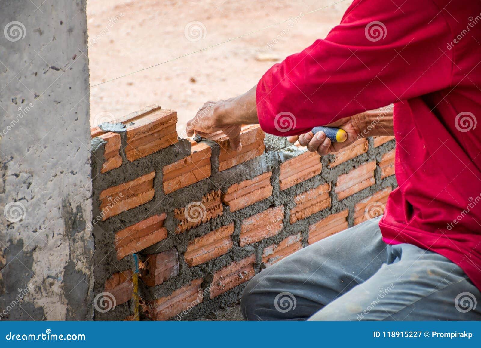 Bauarbeiter, der Ziegelsteine auf Zement für das Errichten setzt
