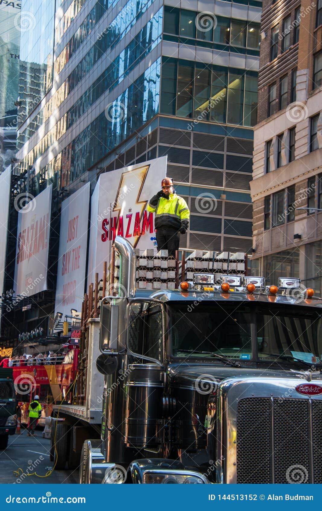 Bauarbeiterstellung auf eine konkrete Last auf einem großen LKW auf einer Allee in Manhattan, New York