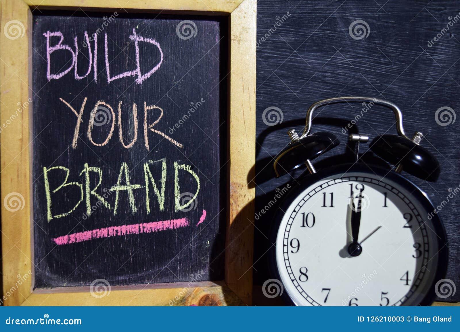 Bauen Sie Ihre Marke auf buntem handgeschriebenem der Phrase auf Tafel auf