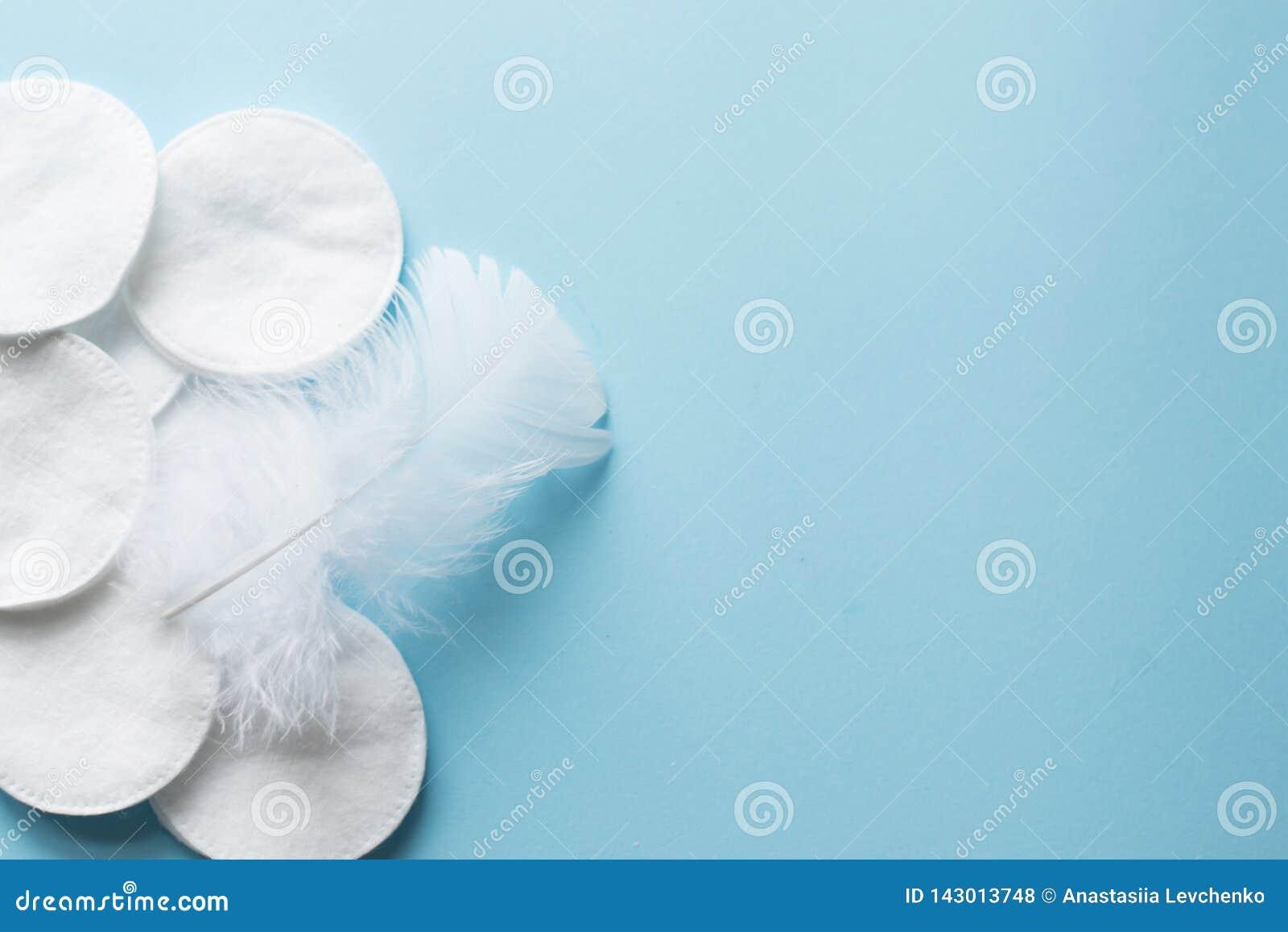 Baumwollauflagen mit weißer Feder auf blauem Hintergrundabschluß oben Kopieren Sie Platz Beschneidungspfad eingeschlossen