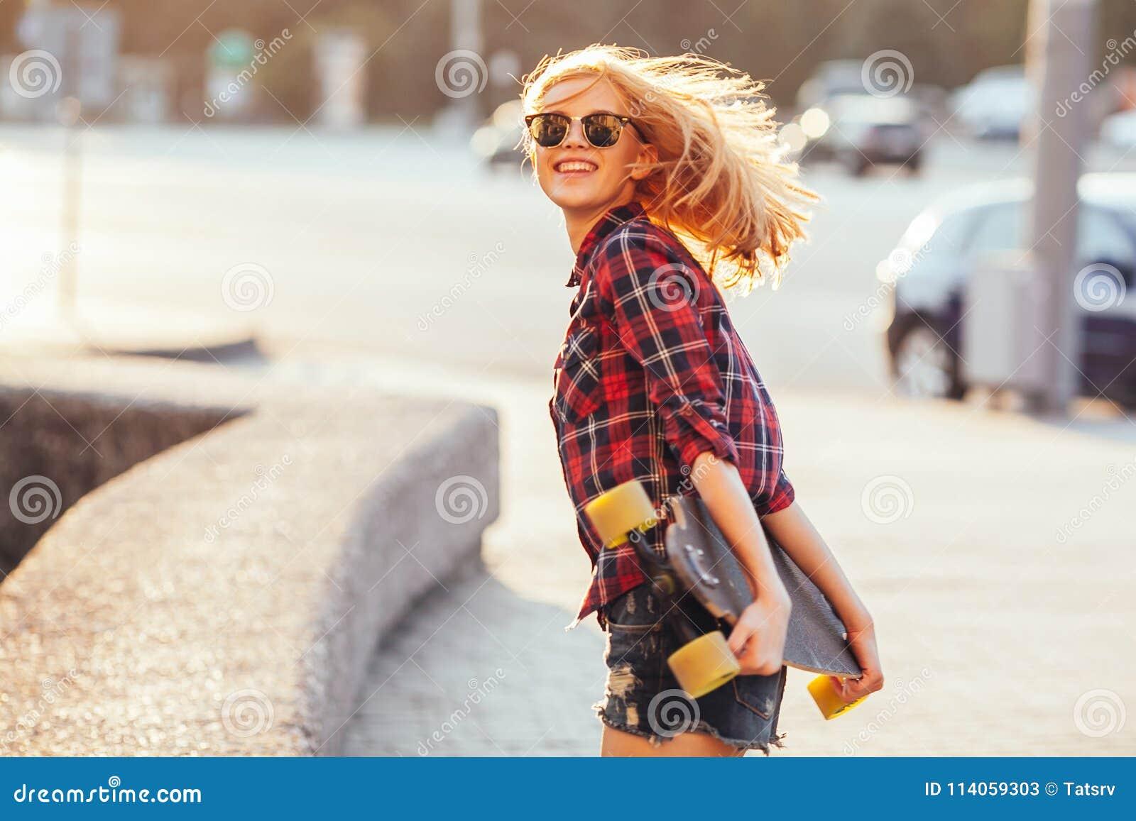 Bawi się szczęśliwej dziewczyny pozuje w lecie z deskorolka Elegancka szczęsliwa modniś kobieta z kolorowym longboard w zmierzchu