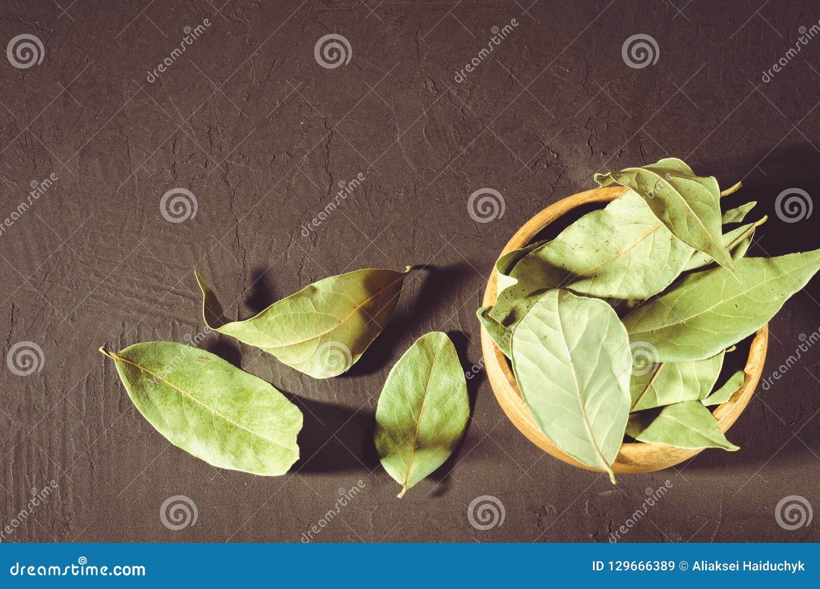Bay leaf in a wooden bowl/bay leaf in a wooden bowl on a black s
