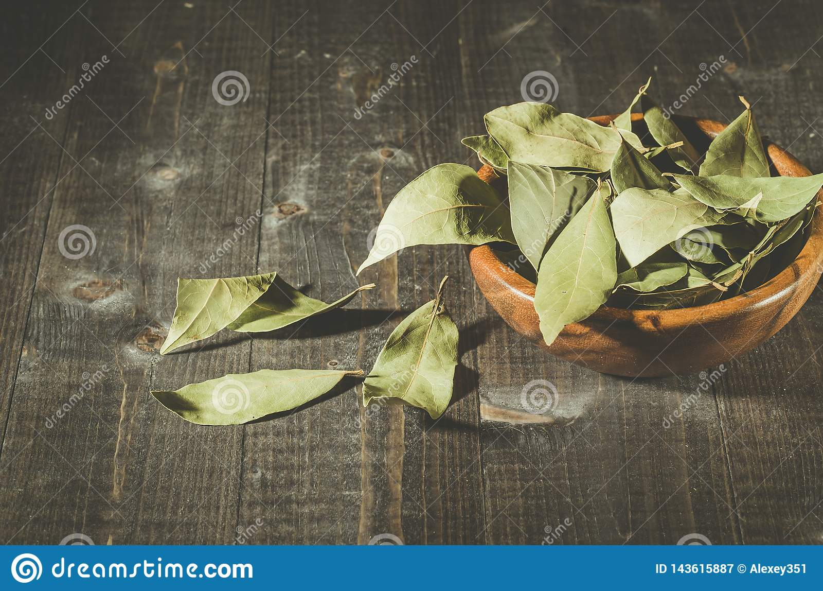 Bay leaf in a wooden bowl/bay leaf on a wooden surface dark wooden background