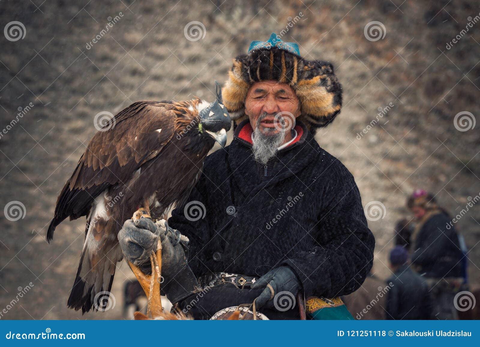 Bayan-Olgii Mongoliet - Oktober 01, 2017: Guld- Eagle Festifal Stående av pittoreska gamla Greybearded mongoliska Hunter Berkutch