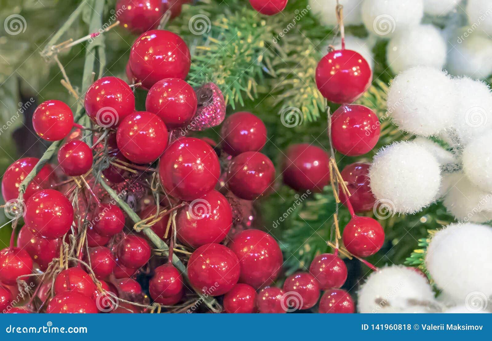 Bayas rojas y bolas mullidas blancas en el fondo del árbol de navidad