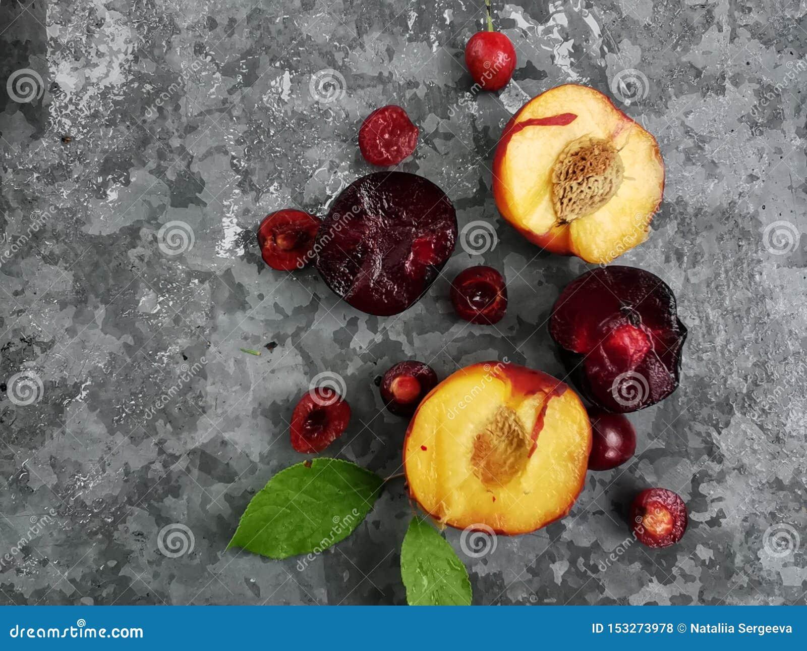 Bayas y frutas maduras frescas del verano, melocotones, albaricoques, cereza y ciruelo en una placa redonda en la tabla