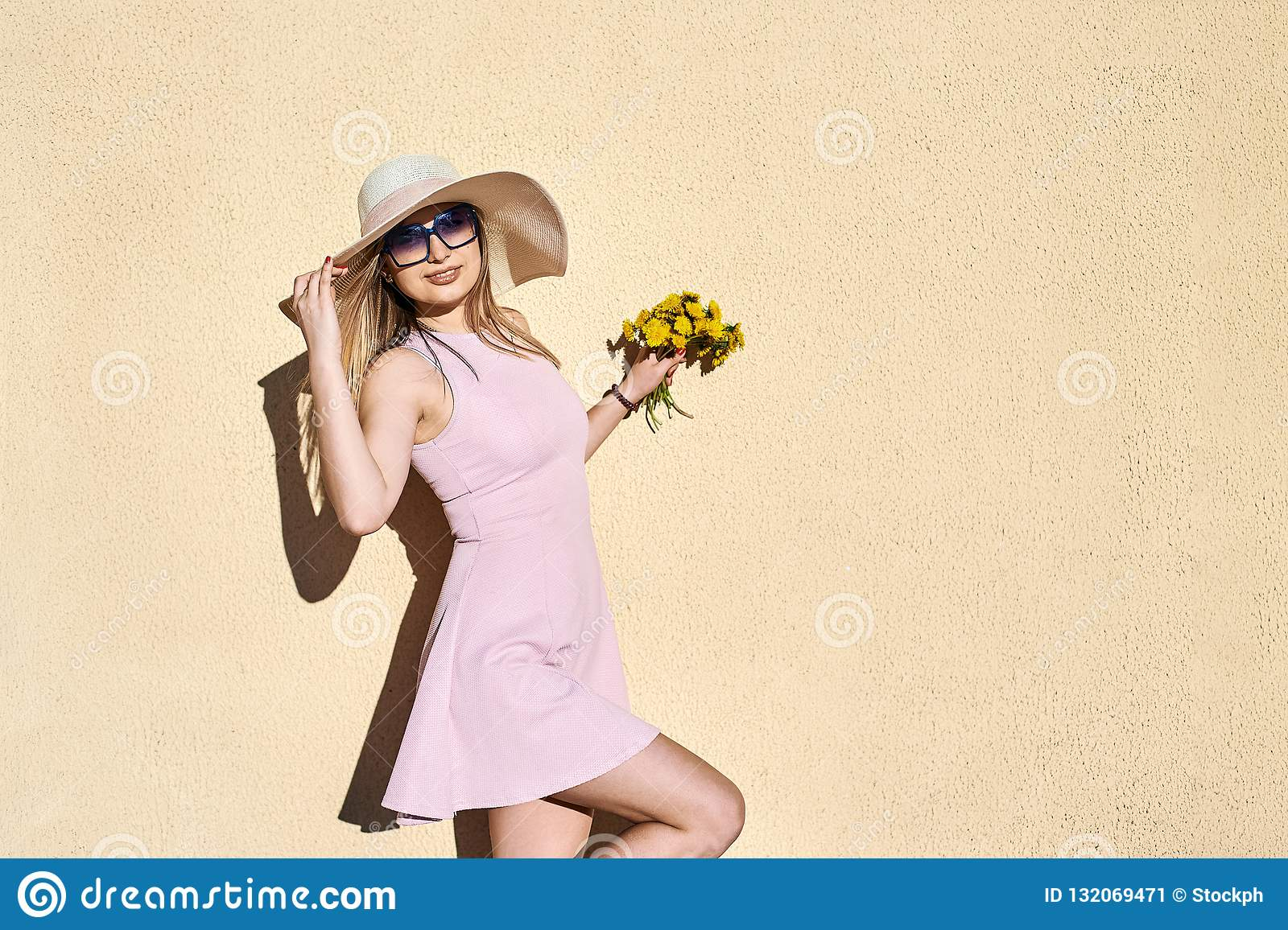 Bbeautiful, lovely, girl in a pink dress, in a straw hat smiling, posing portrait against a yellow wall