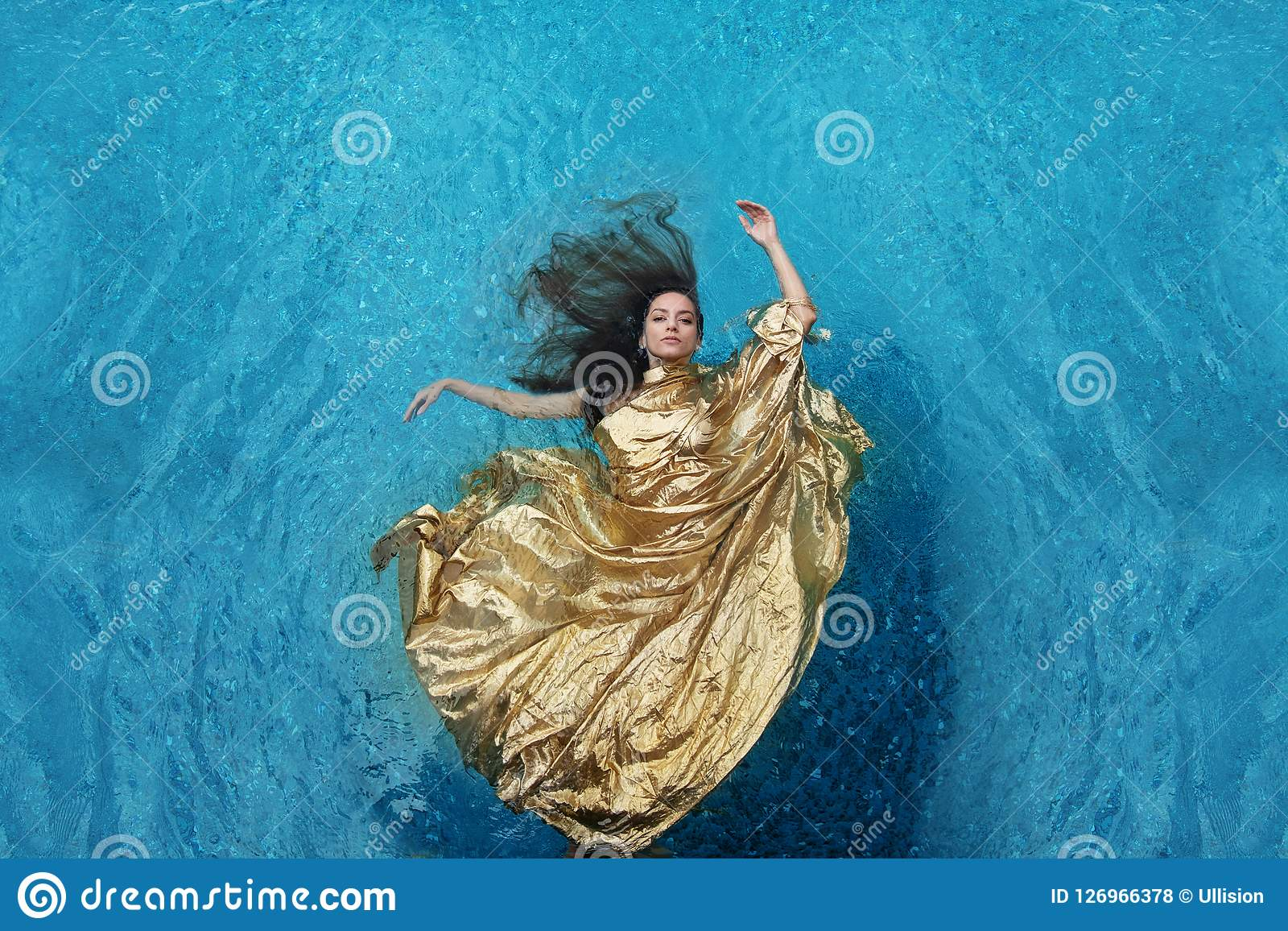 Bbeautiful młoda kobieta w złoto sukni, wieczór suknia unosi się weightlessly elegancki unosić się w wodzie w basenie