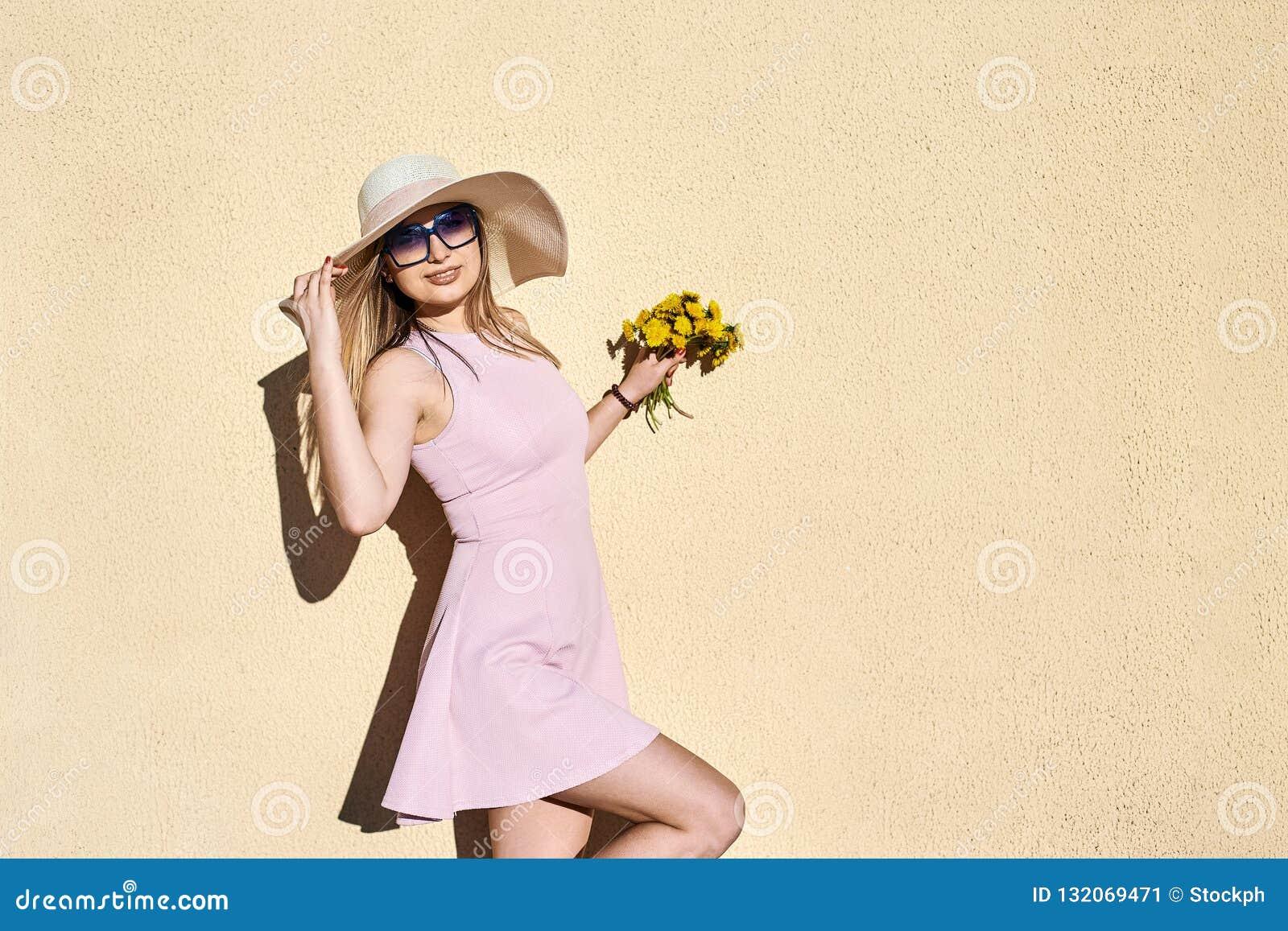 Bbeautiful som är älskvärd, flicka i en rosa klänning, i le för sugrörhatt som poserar ståenden mot en gul vägg