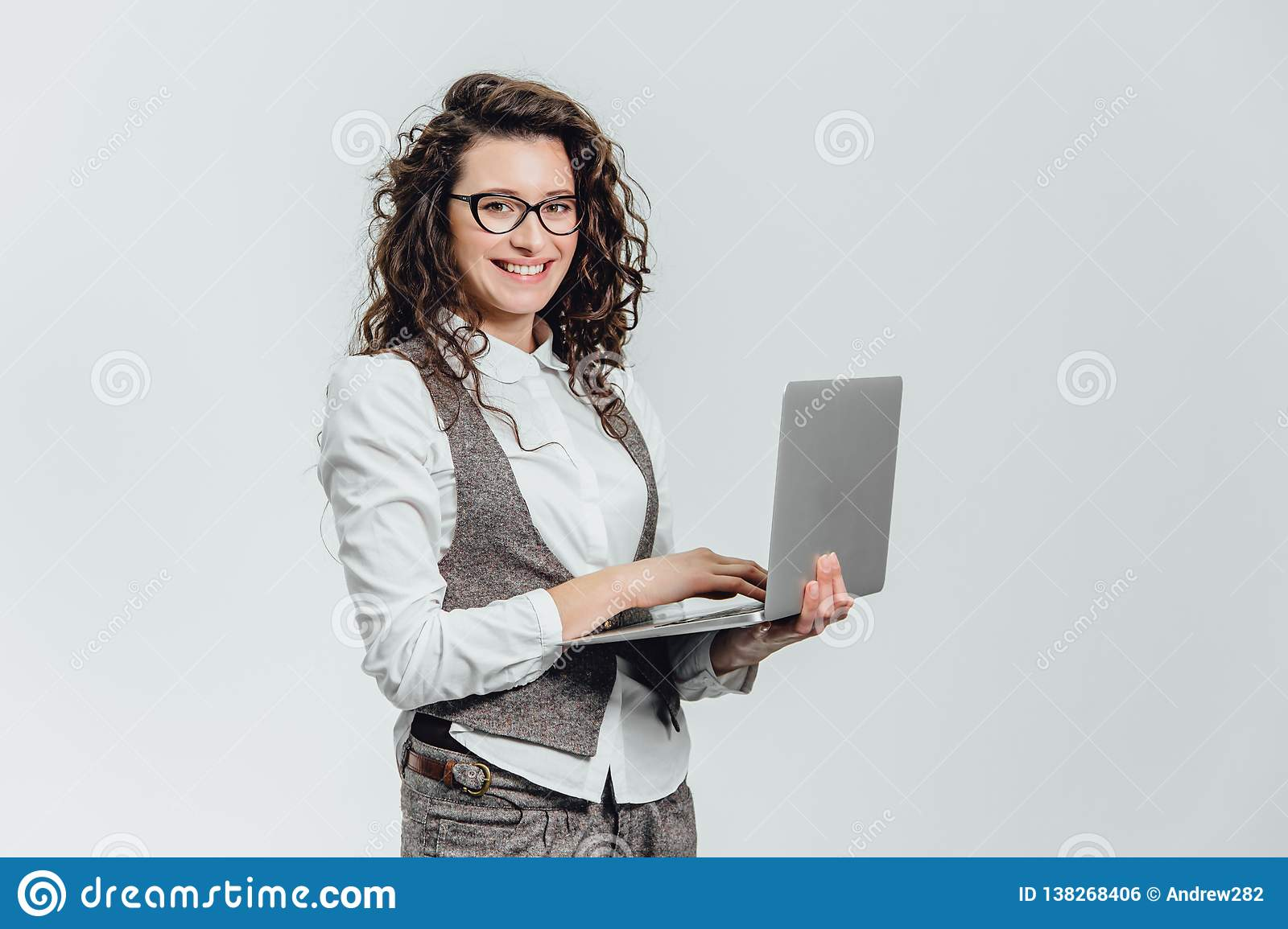 BBeautiful young girl smiles. Works on a laptop in glasses and a white shirt
