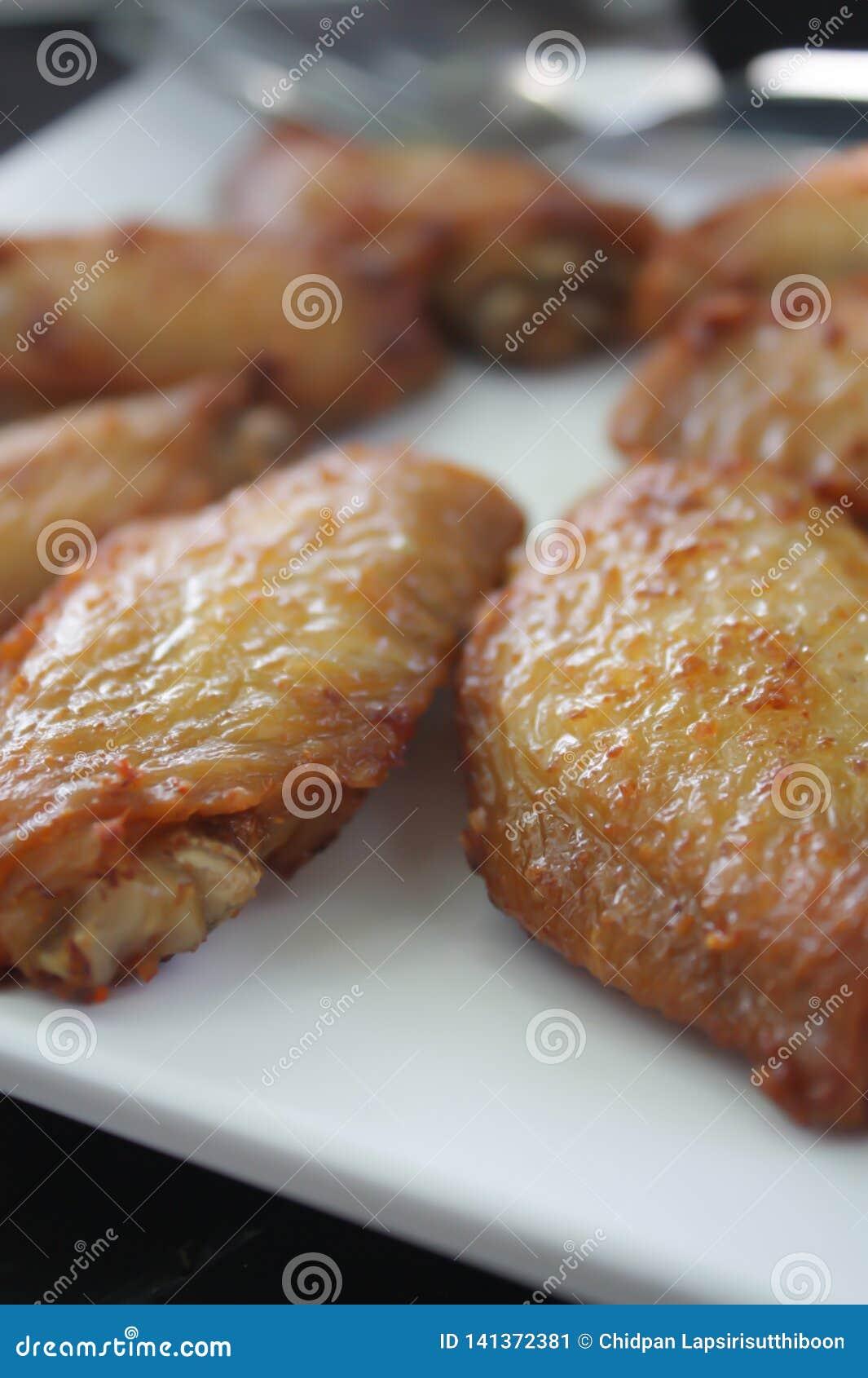 Bbq-Hühnerflügel auf einer weißen Platte dienten auf einem schwarzen Holztisch