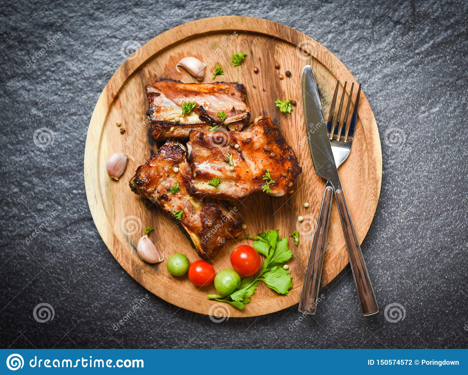 Bbq pork ribs grilled with tomatoes herbs and spices on wooden tray - Roasted barbecue pork spare rib sliced