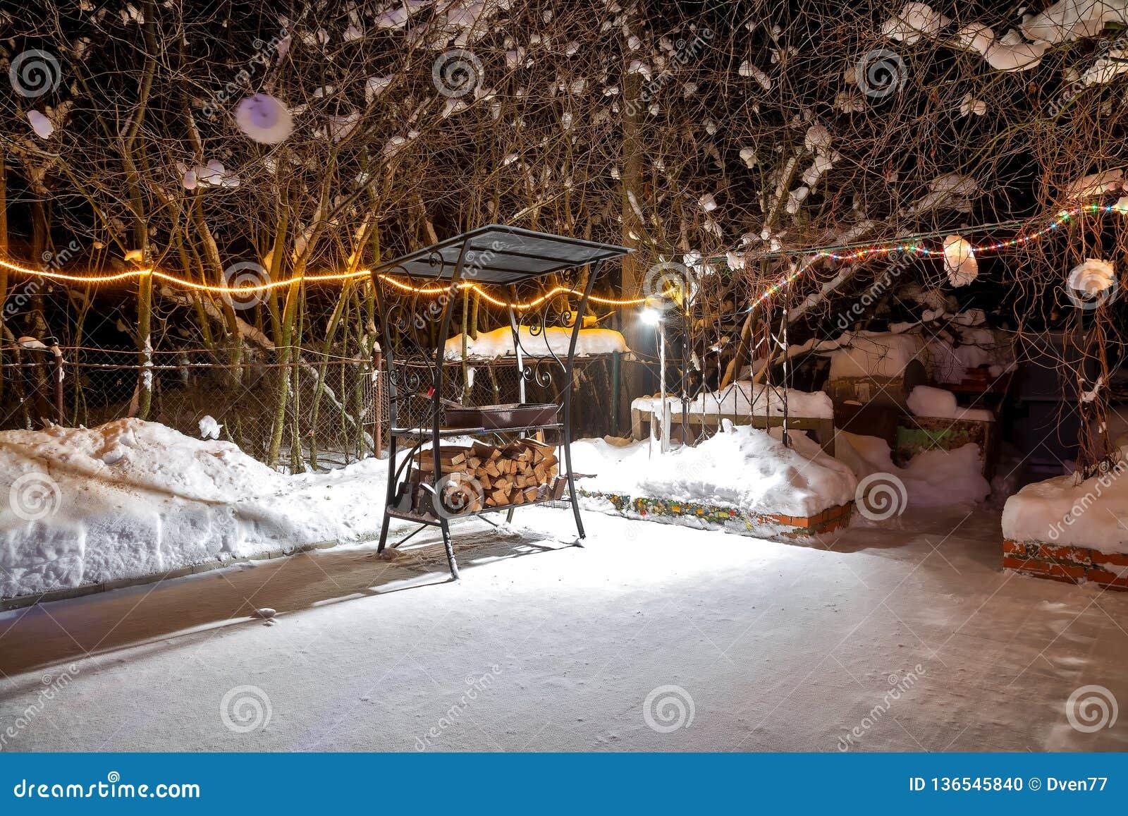 BBQ près de la maison pendant l hiver La nuit, guirlandes brûlent, il neige Terrain de jeu vide Ils étendent le bois de chauffage