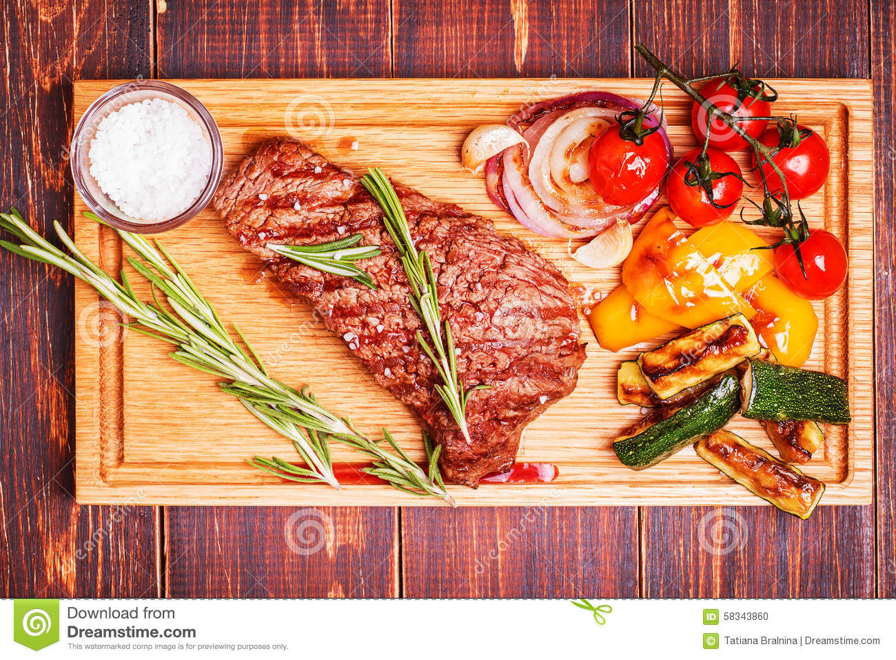 bbq steak with grilled vegetables on cutting board stock