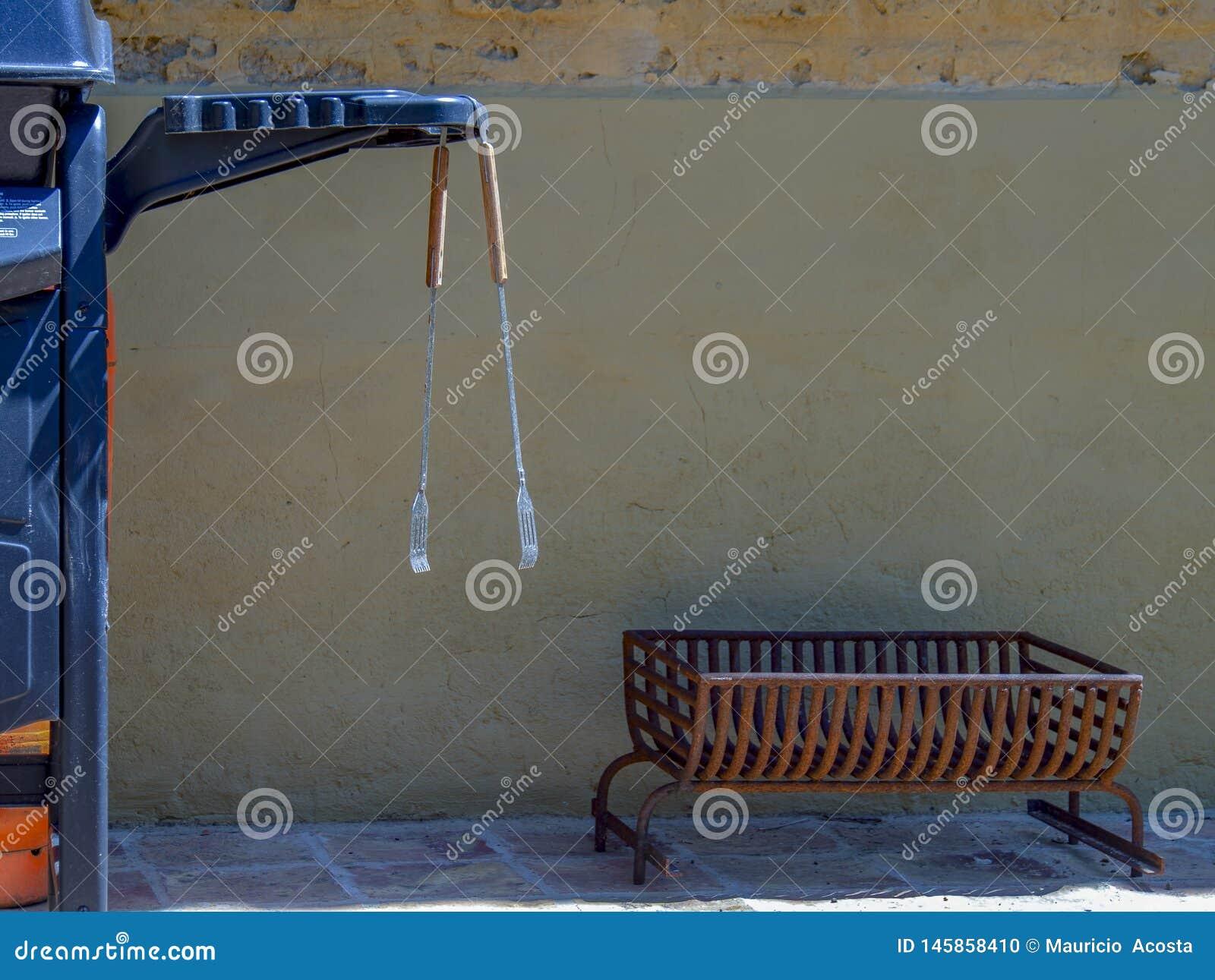 Bbq-tång som hänger från ett BBQ-galler