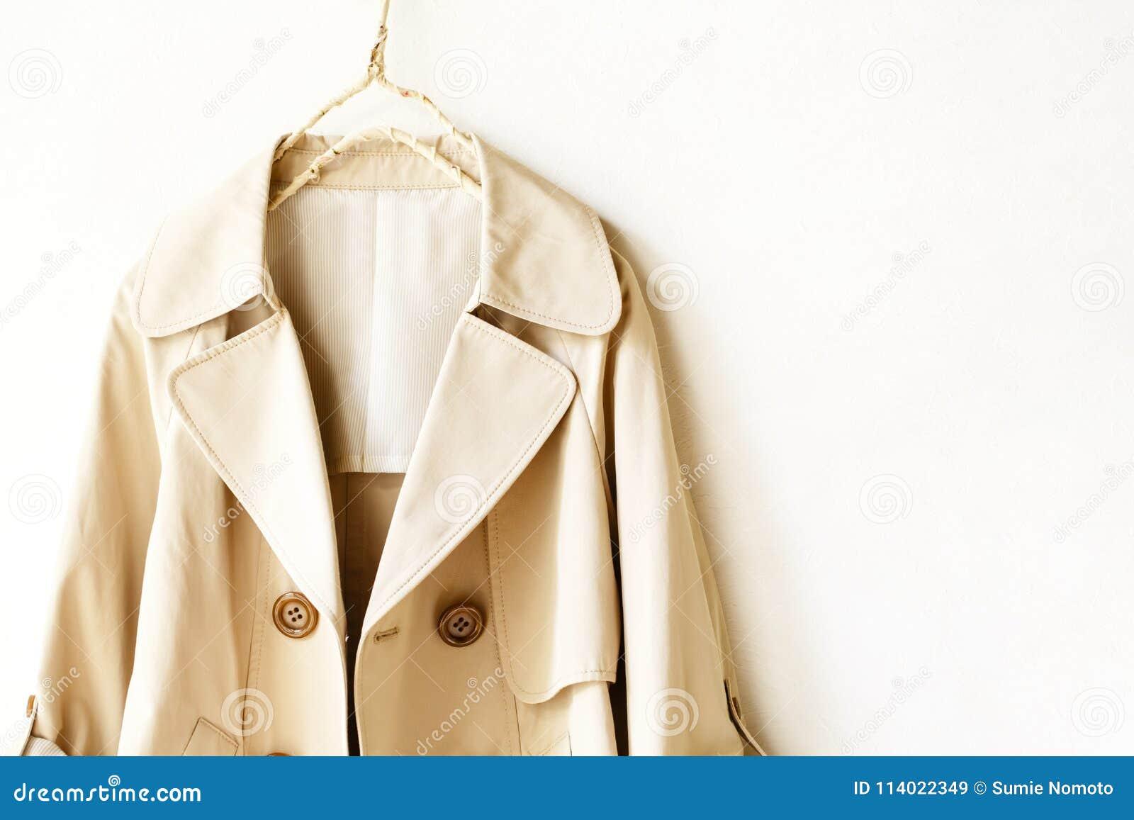 Beżowy elegancki okopu żakiet odizolowywający nad bielem