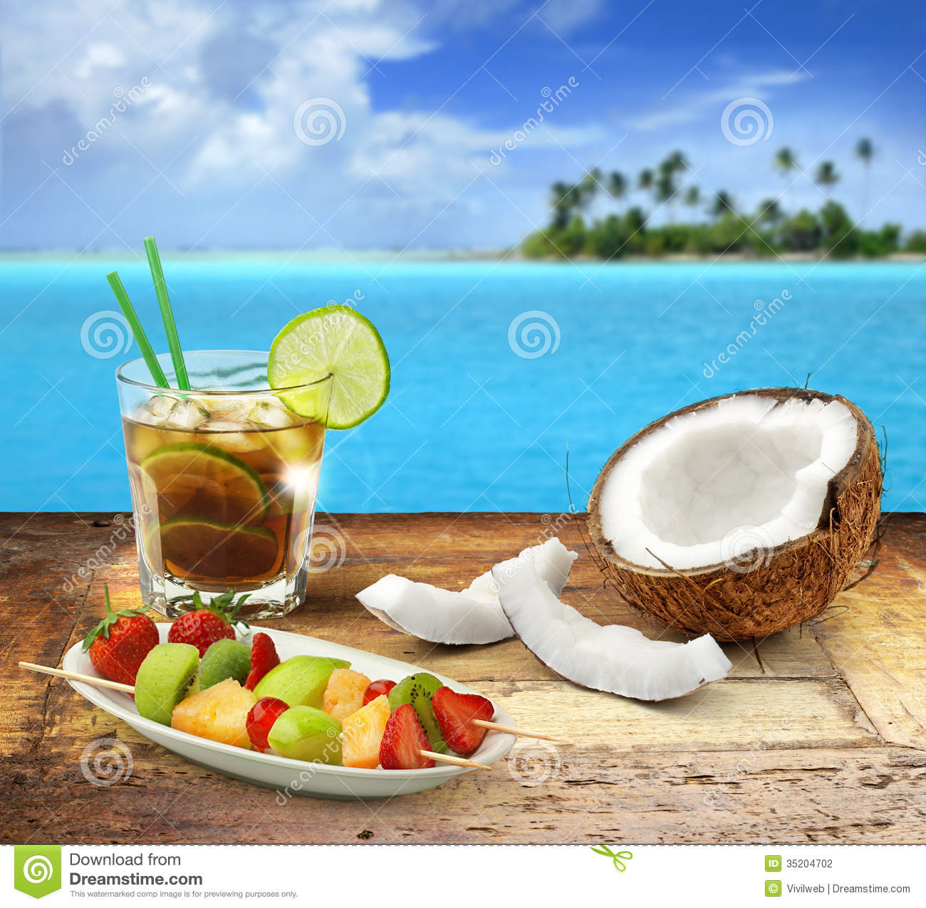 Cuba libre and tropical fruit on a wooden table in a polynesian ...