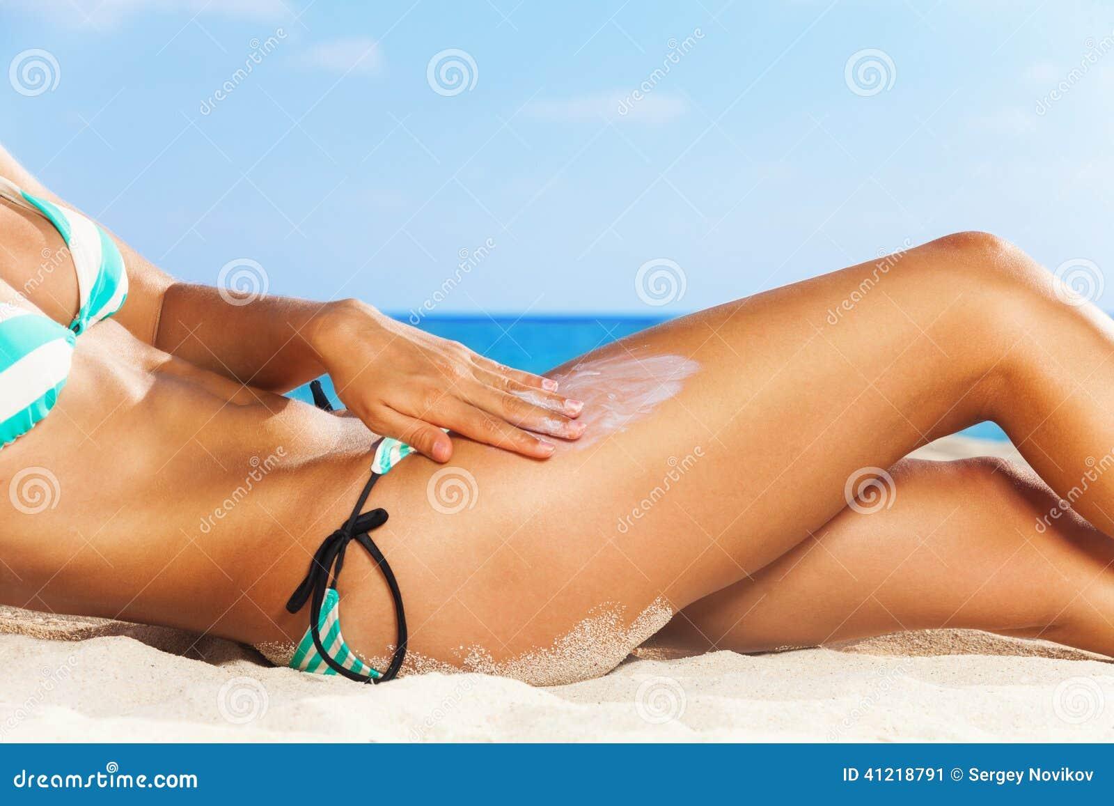 Beach applying sun cream