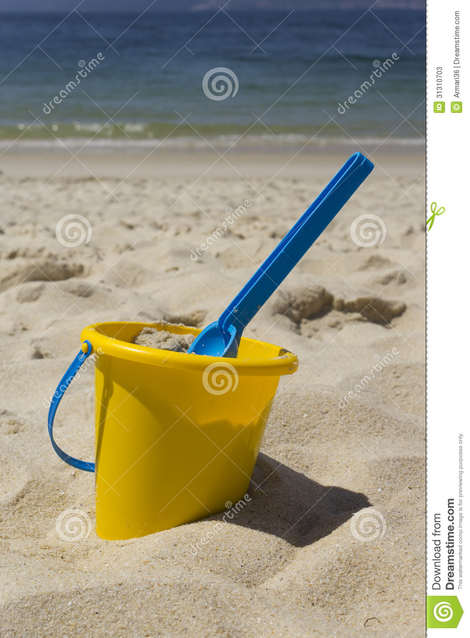Picture of a bucket with his shovel in the sand at the beach.