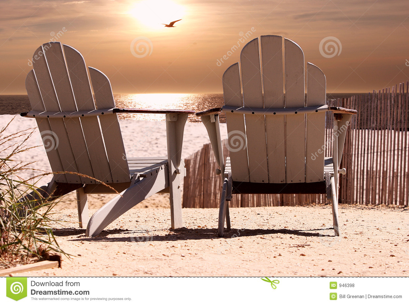 Chairs on beach as the sunsets with seagull flying across background.